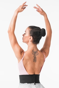 Young ballerina with bow and tiptoe tattoo on her back against white backdrop