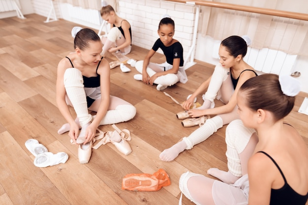 Young ballerinas change shoes to pointe shoes.
