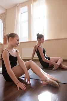 若いバレリーナの練習。 10代のスポーツ。ダンスクラスの物思いにふける女性、ストレッチする可愛い女の子。子供の頃からの感性。ジムの背景、健康的な十代のライフスタイル、女性らしさの概念