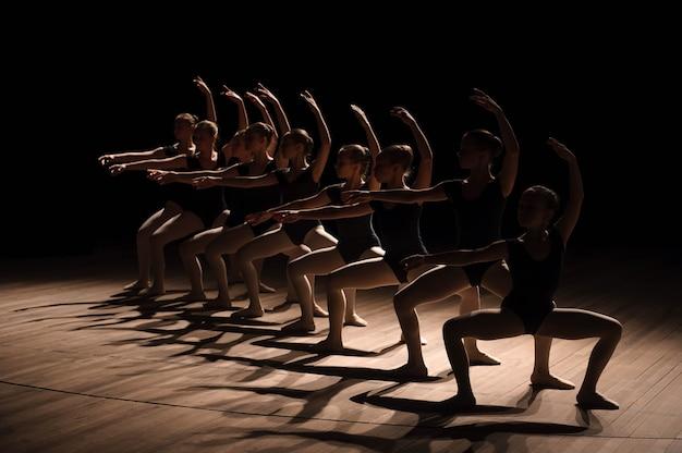 振り付けのダンスを練習している若いバレリーナは、バレエ学校での練習中に優雅に一斉に腕を雨が降っています。