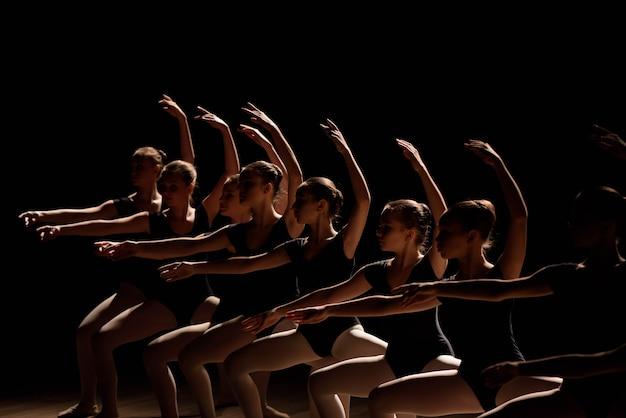 안무 춤을 연습하는 젊은 발레리나는 발레 학교에서 연습하는 동안 우아하게 조화롭게 팔을 비가 내립니다.