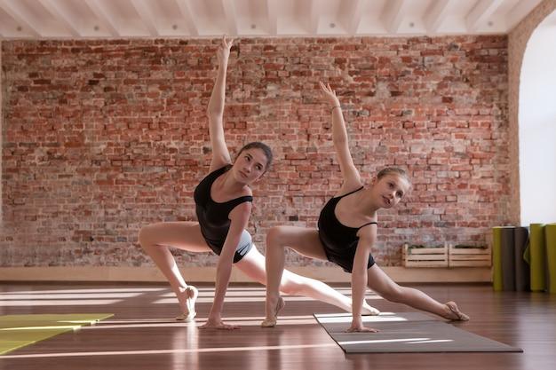若いバレリーナのトレーニング。同期された作業。女の子のためのスポーツ、クラスで踊る女性。自由空間、健康的なティーンエイジャーのライフスタイル、女性らしさの概念を持つジムの背景