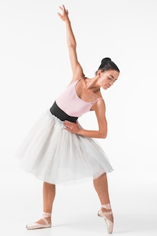 Young ballet dancer dancing in front of white backdrop