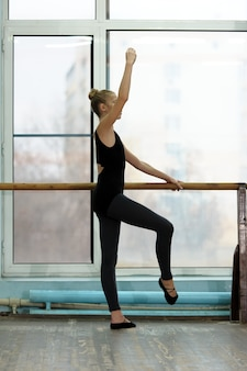 Young ballet dancer exercising at the barre in studio