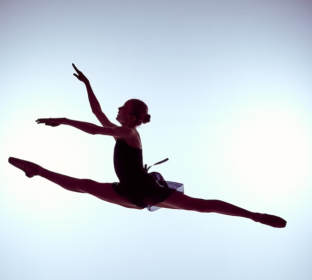 Молодой артист балета прыгает на сером фоне балерина носит синее платье