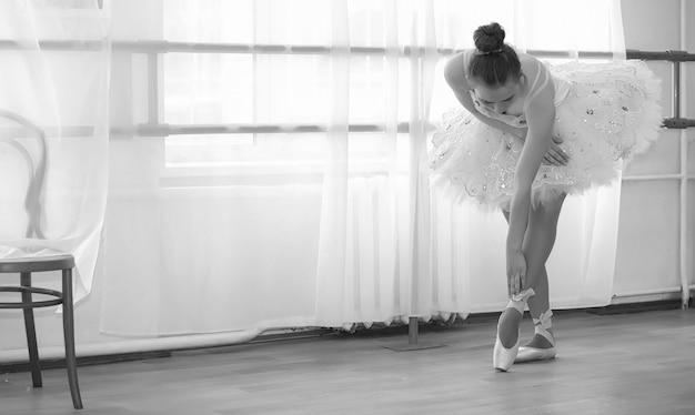 Юная артистка балета на разминке. балерина готовится выступить в студии. девушка в балетной одежде и туфлях месит за поручни.