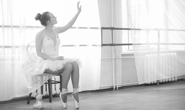 Юная артистка балета на разминке. балерина готовится выступить в студии. девушка в балетной одежде и туфлях месит за поручни. Premium Фотографии