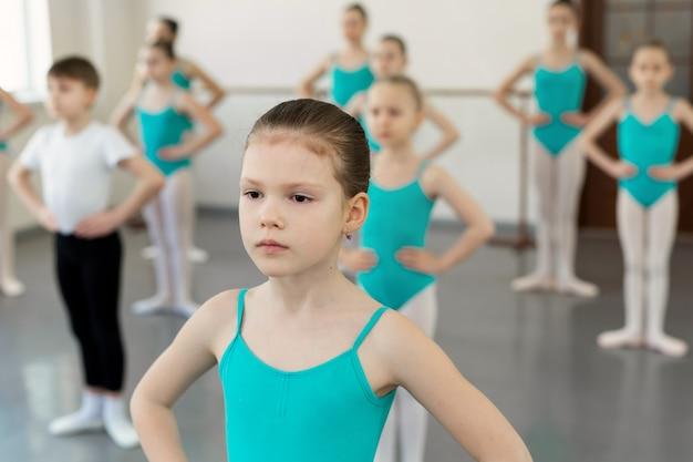 Юные балетницы на трико тренируются в балетном классе