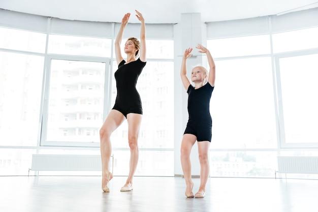 Young ballet teacher and her little student in ballet class