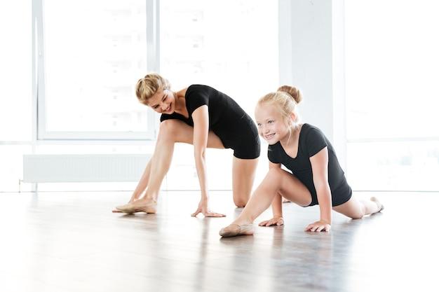 Young ballet teacher and her little student in ballet school