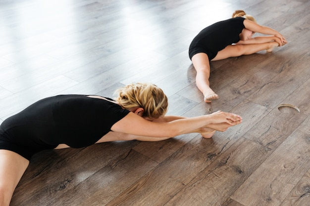 Young ballet teacher and her little student doing stretching exercises on the floor at studio