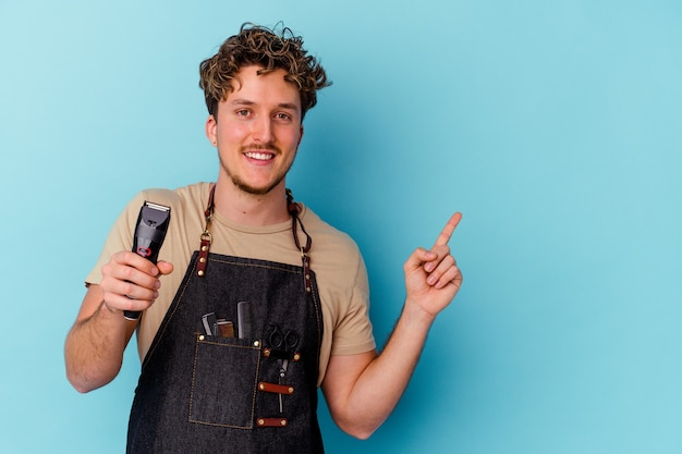 Young barber caucasian man isolated on blue wall smiling and pointing aside, showing something at blank space