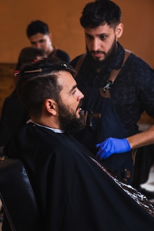 Young barber cutting the beard of a handsome young man - barber cutting his client's hair at the barber shop.