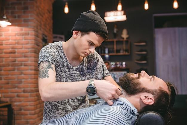 Молодой парикмахер с татуировкой, бреющей бороду своего клиента машинкой для стрижки волос в парикмахерской