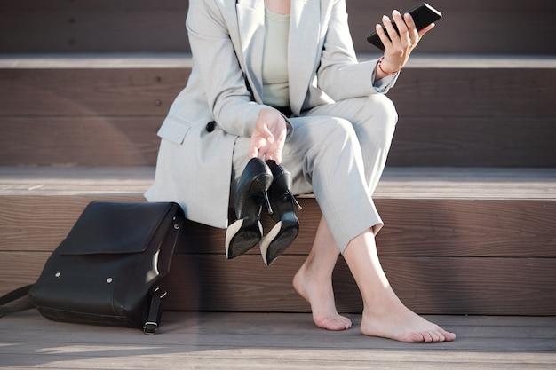 그녀의 스마트폰에서 스크롤하는 젊은 맨발의 사업가