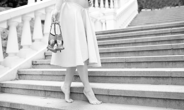 ドレスを着た若い裸足の女性は、一人で草原に立っています。彼女の手にハイヒールの靴のペアを持つつま先。一人でポーズをとる。白と黒の写真。