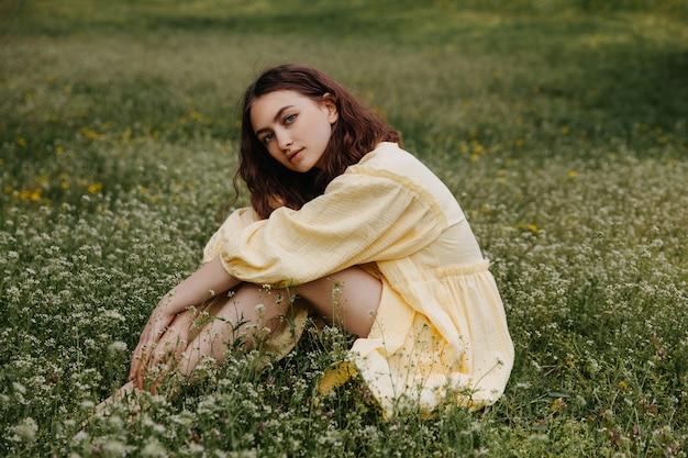 緑の草のフィールドに座っている黄色のドレスを着て若い裸足の女性