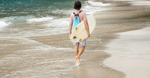 Young barefooted surfer with backpack walking along beach, carrying white bodyboard under his arm, returning home after intensive ride