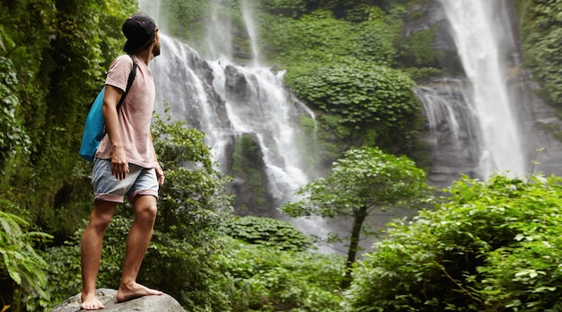 Young barefooted tourist in baseball cap standing on big stone and looking back at waterfall behind him in beautiful exotic nature. bearded traveler enjoying wildlife while hiking in rainforest
