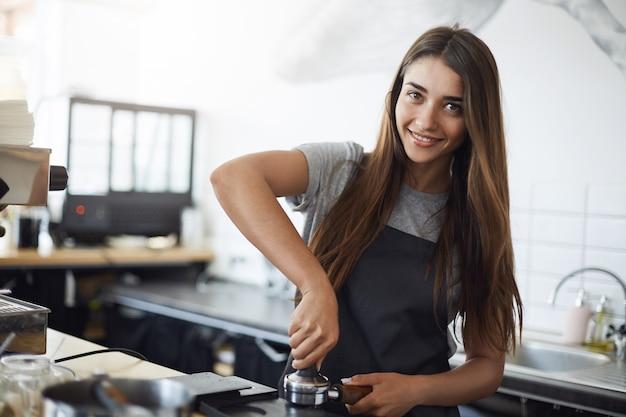 Молодой бариста на работе, глядя в камеру, улыбается, используя тампер для приготовления рюмки эспрессо. концепция работы битника.