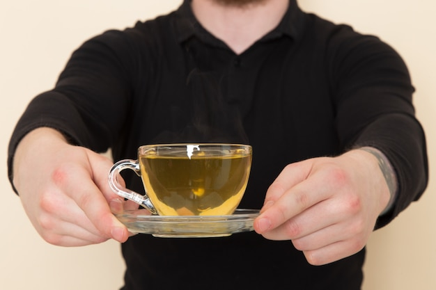 Young barista in black suit holding hot green tea cup