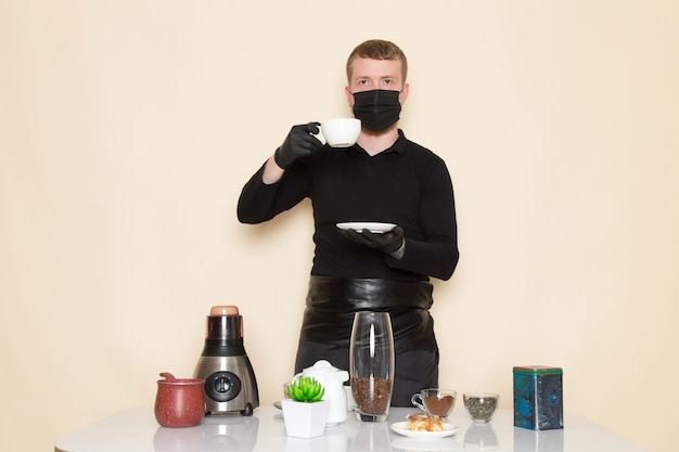 Young barista in black working suit with ingredients and coffee equipment brown coffee seeds wearing black sterile mask on white