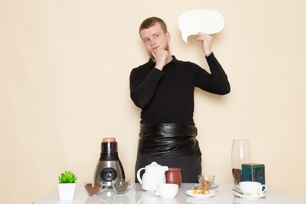 Young barista in black working suit with ingredients and coffee equipment brown coffee seeds on white