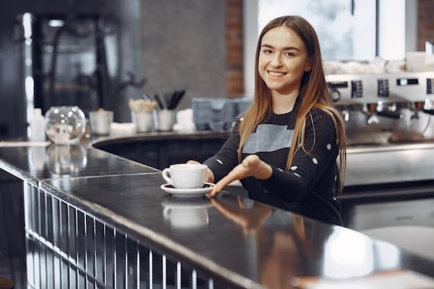 Молодая девушка бариста делает кофе и улыбается