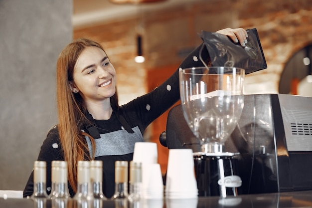 Young barista girl makes coffee and smiles