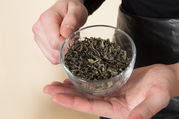 乾燥茶とガラスを保持している若いバリスタ