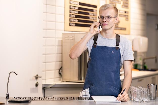 Молодой бариста в фартуке и футболке принимает заказы клиентов по телефону, стоя на рабочем месте и делая записи в блокноте