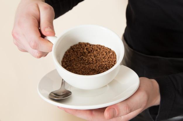 재료와 커피 장비 검은 작업복에 젊은 바리 스타 화이트에 갈색 커피 씨앗