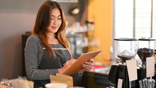 顧客のコーヒーショップカフェから注文を受けてメニューを保持している飲み物メニューを見ている若いバリスタ