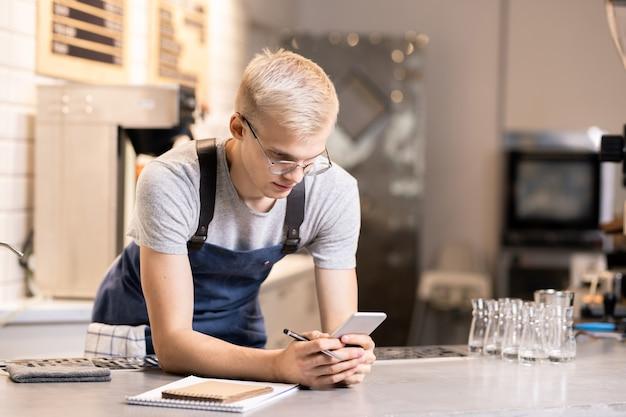 Молодой бариста читает сообщение, прокручивает или отправляет текстовые сообщения на смартфоне, принимая заказы клиентов на работе