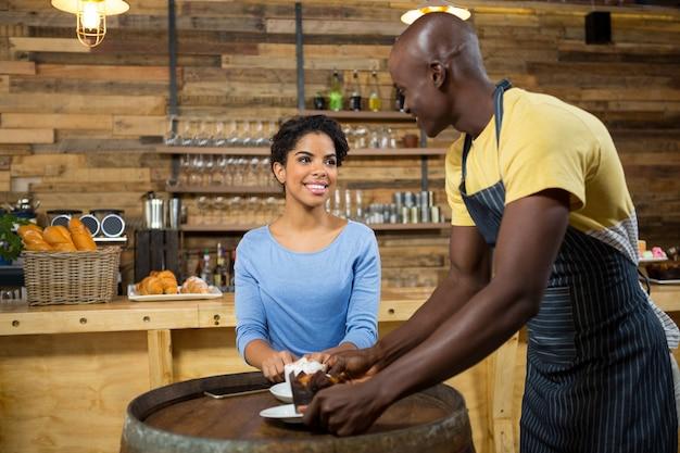 カフェのテーブルで女性にコーヒーを提供する若いバリスタ