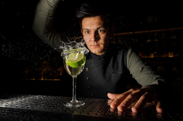 Young barman and a cocktail glass with splashing alcoholic drink and lime in it