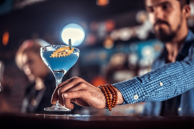 Young barman intensely finishes his creation in the night club