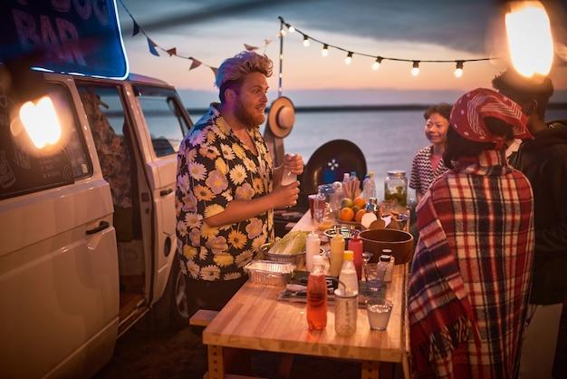 해변 파티에서 젊은 사람들을 위해 알코올 칵테일을 만드는 젊은 바텐더