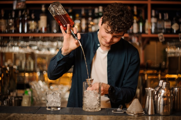 Young barman making a tasty sweet summer cocktail with syrup