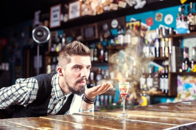 젊은 바텐더는 나이트 클럽에서 음료를 마무리합니다.