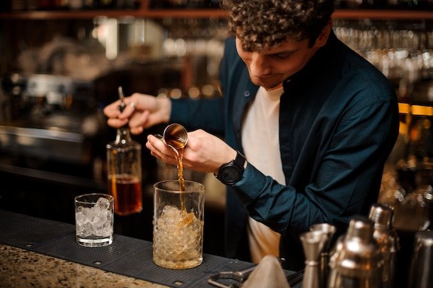 Young barman pouring a sweet syrup into a jar with ice making an alcoholic drink