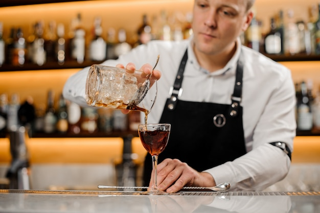 Young bartender adding alcoholic drink into an elegant glass