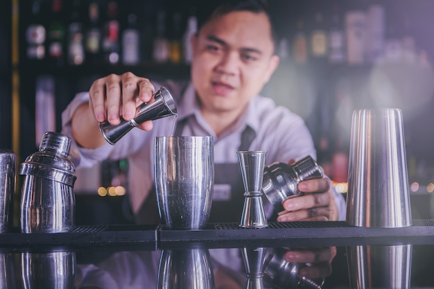 A young bartender is mixing alcohol in a glass to serve customers in a nightclub