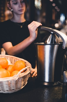 Young bartender juicing oranges in restaurant
