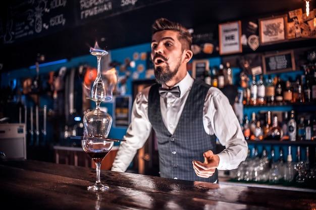 Молодой бармен наливает свежий алкогольный напиток в бокалы, стоя возле барной стойки в баре
