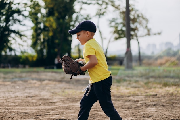 Young baseball player with a baseball glove runs across the field