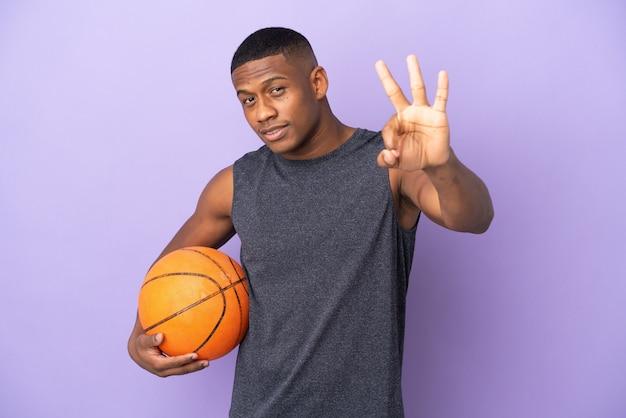幸せな紫色の壁に孤立し、指で3を数える若いバスケットボールラテンプレーヤーの男