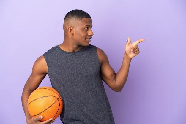 Молодой баскетболист-латинский игрок изолирован на фиолетовой стене, указывая пальцем в сторону и представляет продукт