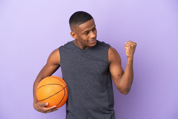 Young basketball latin player man isolated on purple celebrating a victory