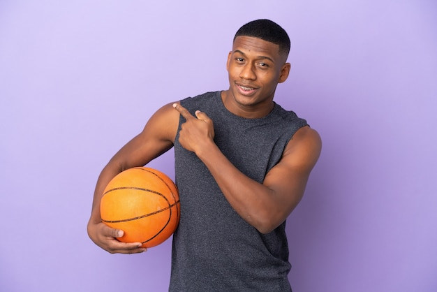 Young basketball latin player man isolated on purple pointing to the side to present a product